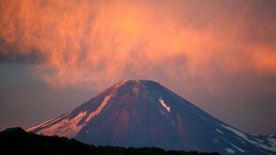 En vulkan med röd rökdimma över sig
