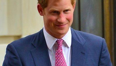 Prins Harry står i en blå kavaj och ser glad ut