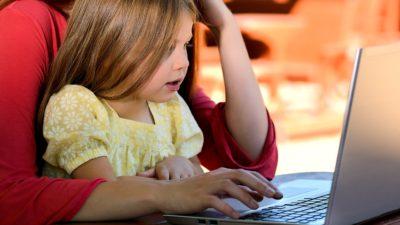 En flicka som tittar på en laptop.