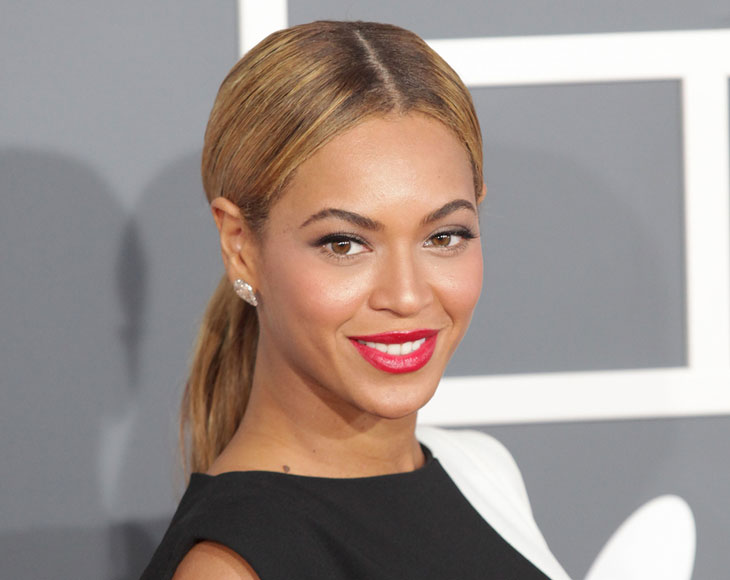 Beyonce står framför en grå vägg. Hon har blonderat hår i en mittbena och hästsvans. Hon har klarrött läppstift och svarta kläder.