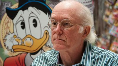 Tecknaren Don Rosa sitter framför en bild av Joakim von Anka