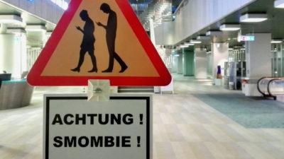En varningsskylt med två människor som tittar ner i sina mobiltelefoner.