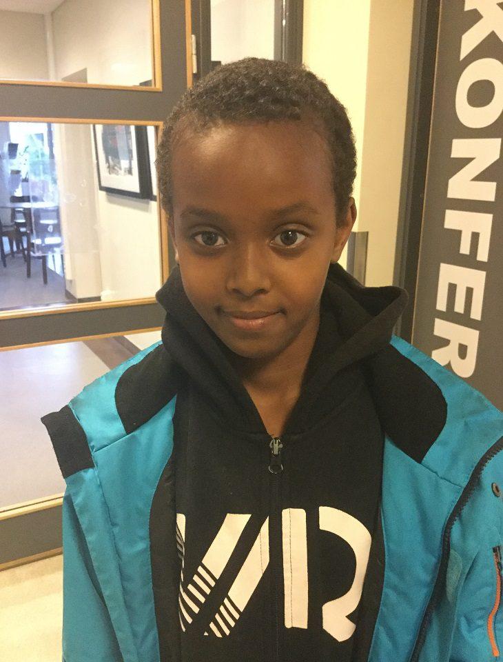 Abdirahman står i en korridor. Han har en svart hoodie och en blå jacka. Han har kort svart hår och tittar lite lurigt mot kameran.