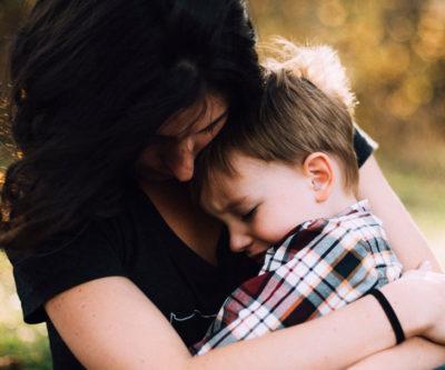 En kvinna som håller om ett ledset barn