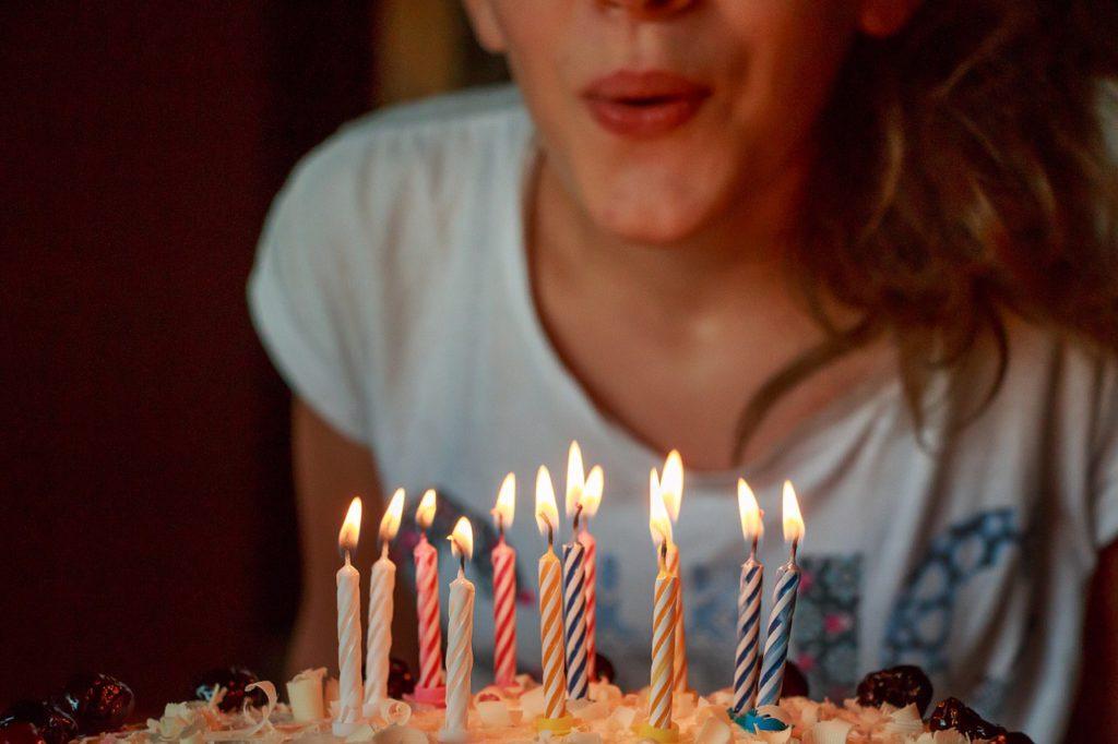 En person blåser ut färgglada ljus på en tårta.