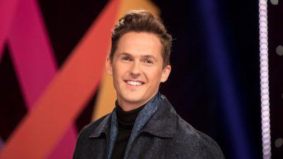 David står framför Melodifestivalens logga. Han har håret bakåtkammat och har på sig en grå jacka. Han ler stort mot kameran.