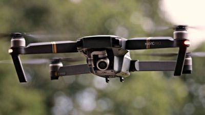 En drönare flyger i luften. Den är grå med fyra pinnar som sticker ut åt varsitt håll. Längst fram syns en kameralins.