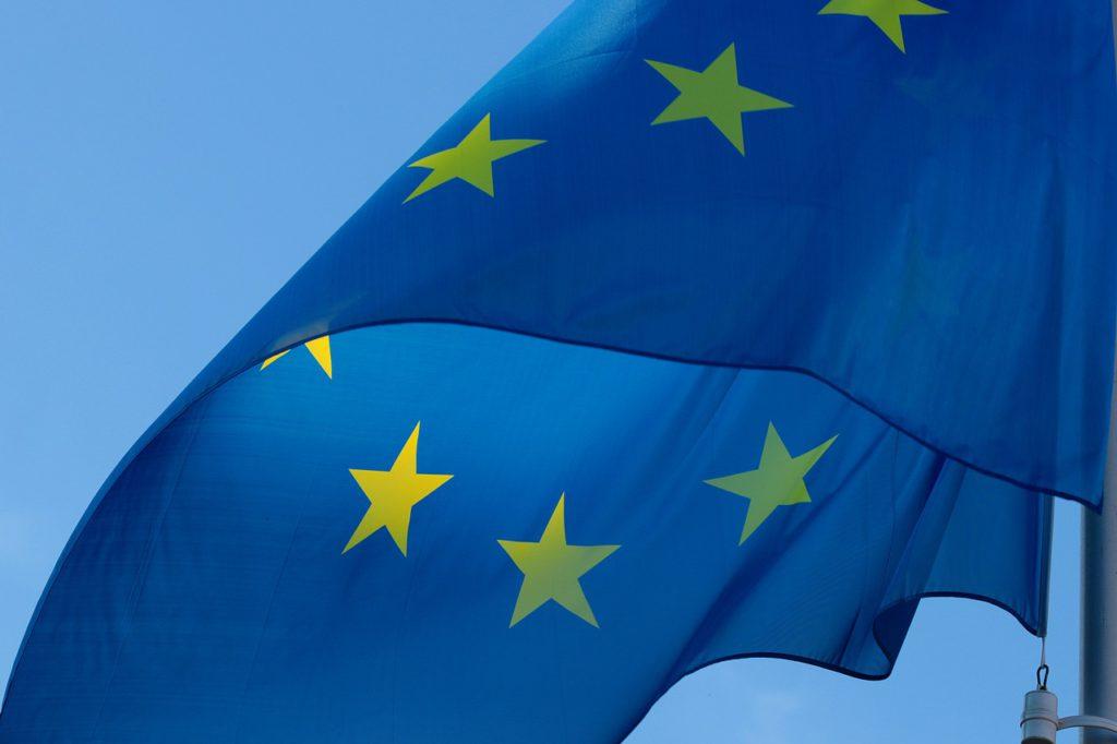 En blå flagga med gula stjärnor som blåser i vinden.