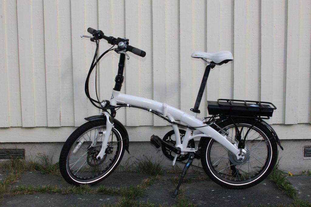 En elcykel står framför en vit vägg. Den har små hjul och en vit ram som är ganska bred. Under pakethållaren syns en liten svart låda.