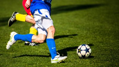 Två fotbollsspelare springer på en plan efter en fotboll