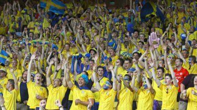 Svenska fotbollssupportrar står på en läktare och hejar på det svenska landslaget.