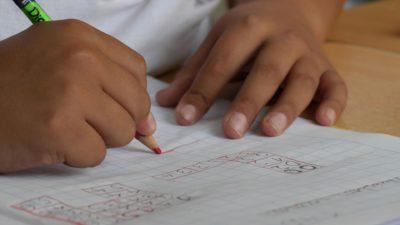 Ett barns händer håller en penna och skriver på ett papper.