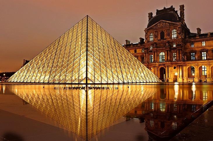 Den stora glaspyramiden utanför Louvren. Den är upplyst och runt den är en sjö.
