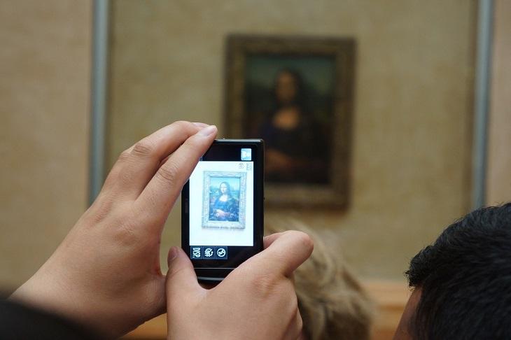 Någon tar en bild med sin mobil av Mona Lisa.
