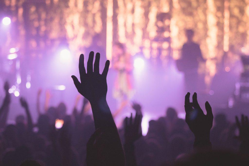 Människor sträcker upp händerna på en koncert
