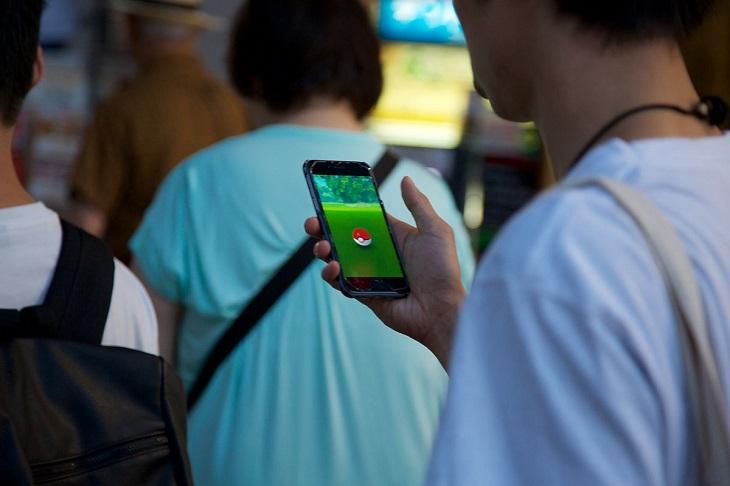 Ryggar på flera människor. Den som står närmast har en mobil i handen. På skärmens syns Pokémon Go-spelet.