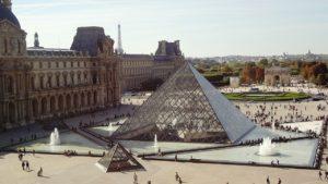 En bild över Louvren. Utanför den slottsliknande byggnaden syns en stor glaspyramid mitt i en sjö av vatten.