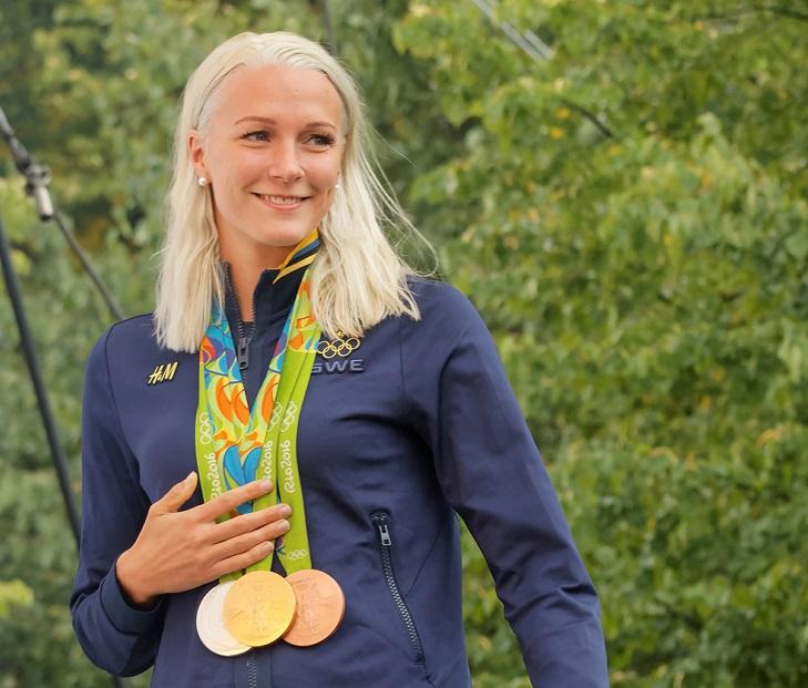 Sara Sjöström. Bakom henne syns massa gröna löv. Hon har långt ljust hår och en blå jacka. Runt halsen hänger flera medaljer i band.