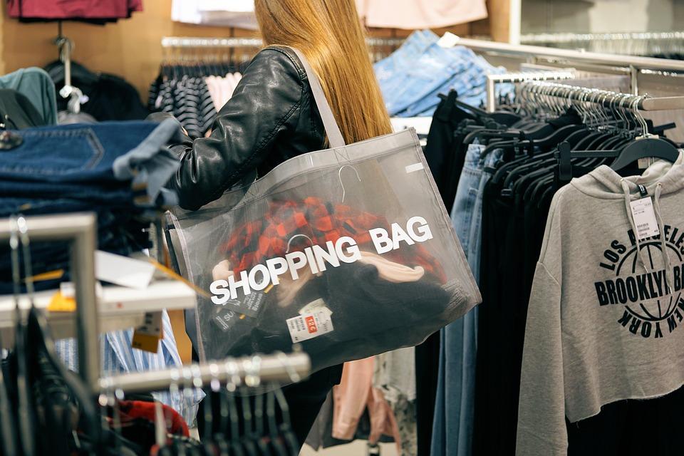 En tjej står bland kläder med en shopping väska full av kläder.