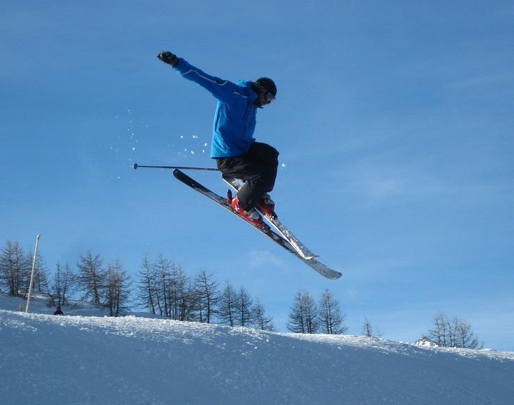 En skidåkare i blå jacka hoppar med sina skidor och armarna utsträckta