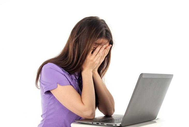 En tjej i lila tröja sitter framför en dator. Hon håller händerna för ansiktet och låter håret ramla fram.
