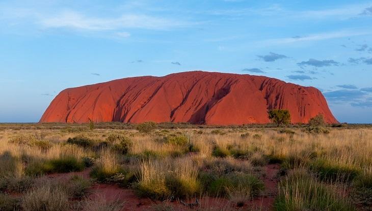 Uluru. Det är en stor röd klippa, som är mer lång än hög, och som är rundad upptill.
