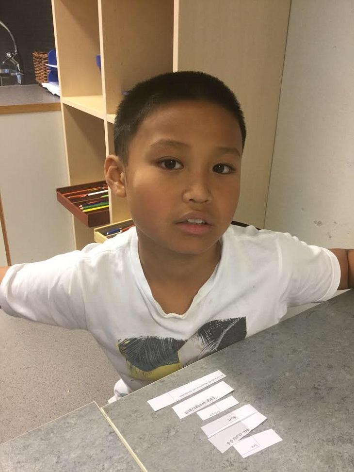 Vincent sitter vid ett bord och tittar upp mot kameran. Han har vit t-shirt och kort svart hår.