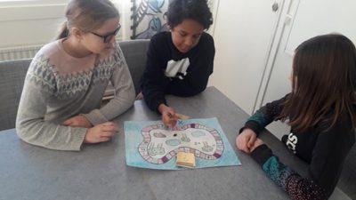 Tre elever sitter runt ett bord i ett klassrum och spelar ett spel. Spelet föreställer en stig runt några träd.