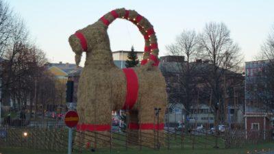 En julbock i halm med röda band