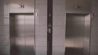 Bilden föreställer två hissdörrar, sida vid sida. Dörrarna är gjorda i ett silvrigt metallmaterial. Runt om dem är det grått kakel.