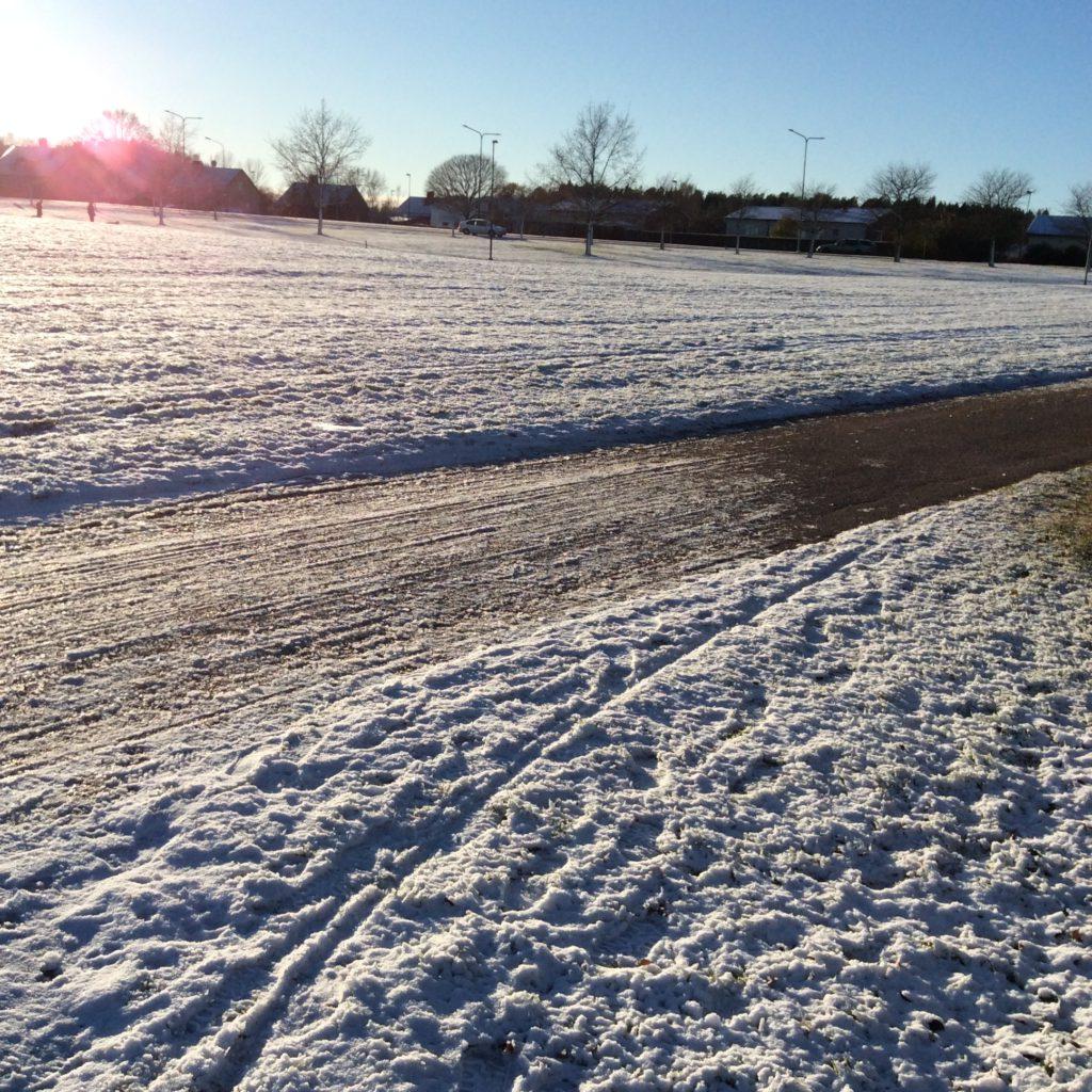 Bilden föreställer en cykelbana med snö på båda sidor. I övre, vänstra kanten skymtar solen.