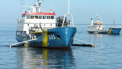 Ett av Kustbevakningens fartyg som kan bogsera båtar. Det är ett medelstort fartyg med ett blått däck. I högra kanten av bilden syns en till båt som är Kustbevakningens.