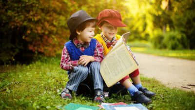Två barn sitter och läser en bok tillsammans på en gräsmatta.