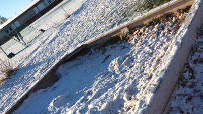 En sandlåda täckt i snö. Solen lyser klart.
