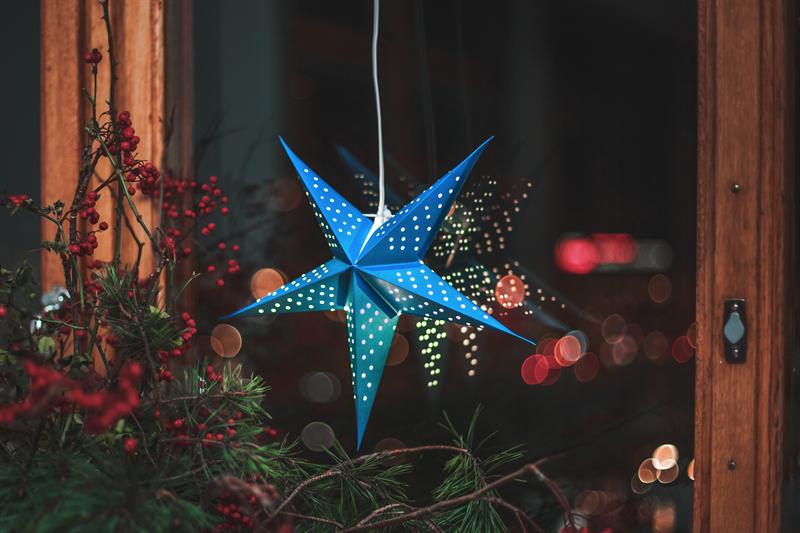 Bris blå julstjärna hänger i ett fönster