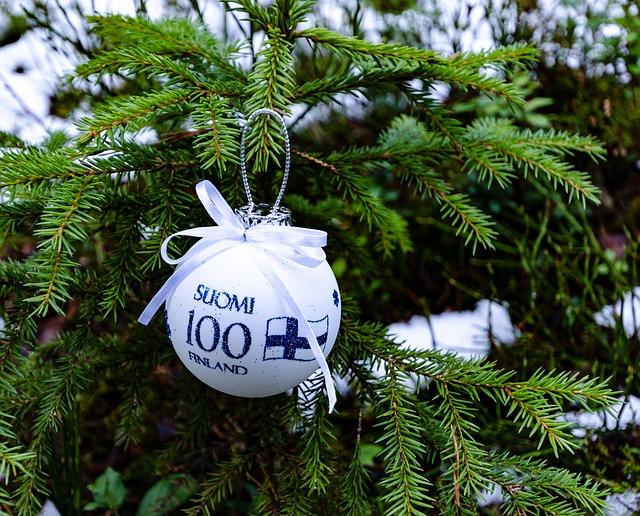 En vit julgranskula där det står Finland 100 på finska och svenska