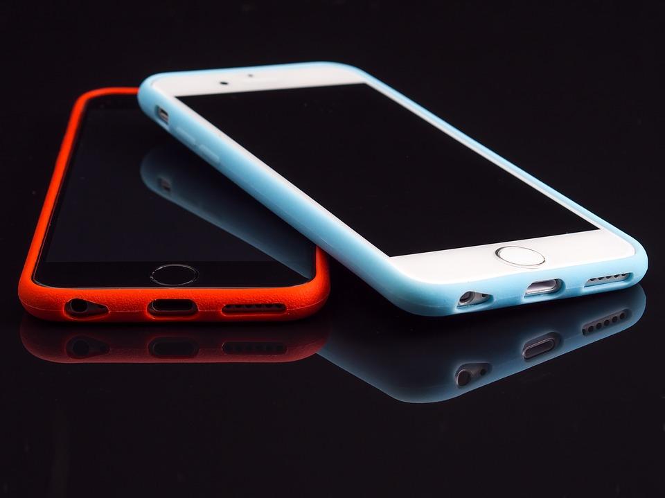 Två iPhones en med ett rött fodral och en med ett vitt fodral.