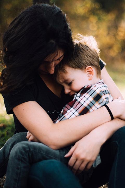 En kvinna tröstar ett barn som sitter i hennes famn