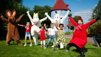 Fyra barn sträcker ut armarna och jublar tillsammans med karaktärerna Sniff, Snorkfröken, Mumin och Lilla My. Bakom dem står Muminhuset.