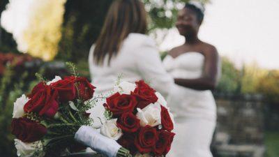 Två kvinnor som ska gifta sig står och håller händer med två rosbuketter framför dem.
