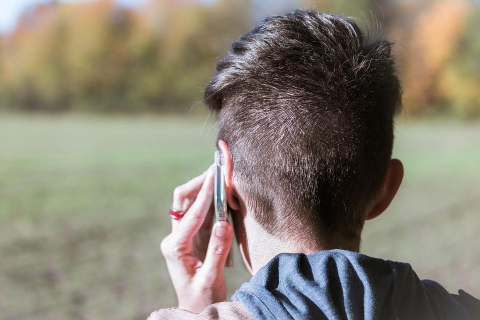 En person med kort hår bakifrån pratar i telefon