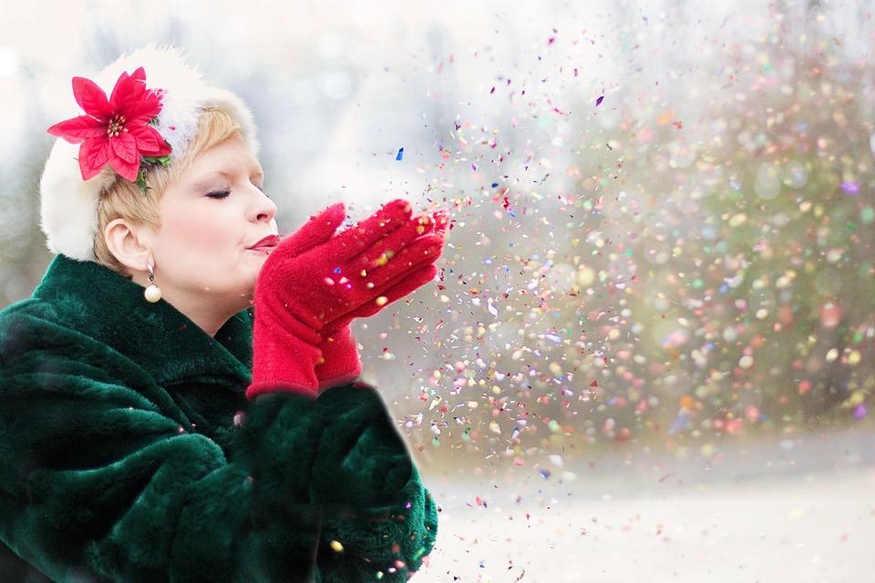 En kvinna med grön jacka och röda handskar blåser glitter från sina händer
