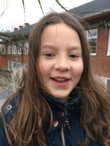 Lea ståt utomhus med en röd byggnad i bakgrunden. Hon har svart jacka och brunt långt hår som blåser i vinden.