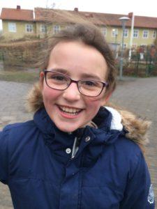 Elina ler stort mot kameran. Hon har glasögon och brunt hår i hästsvans.