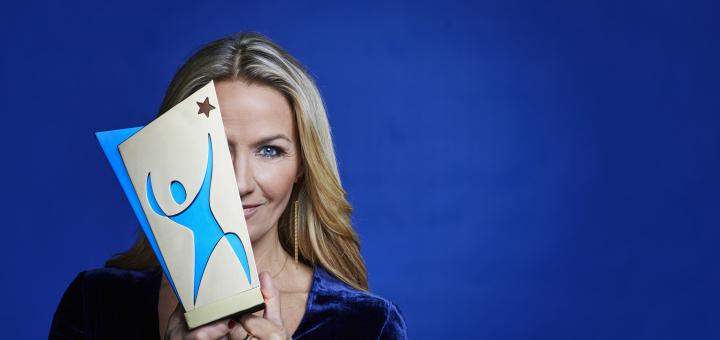 Kristin Kasperson håller i ett pris som delas ut under idrottsgalan.