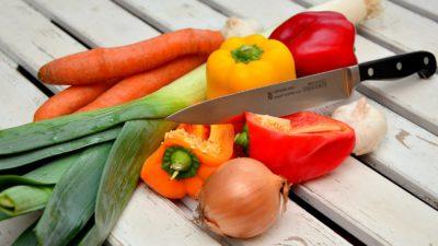 Grönsaker ligger på ett bord tillsammans med en kniv