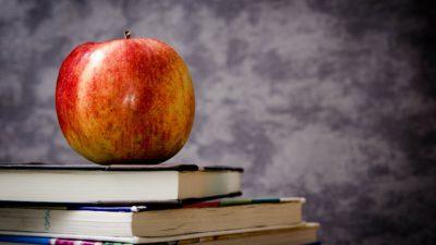 Ett äpple ligger på två böcker