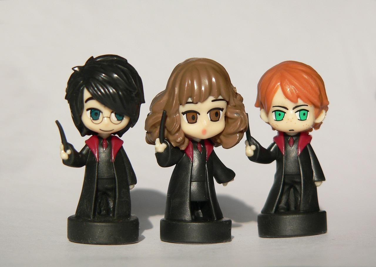 Tre leksaksfigurer. De har alla svarta mantlar trollstavar. En har svart hår, en har rött hår och en har långt brunt hår.