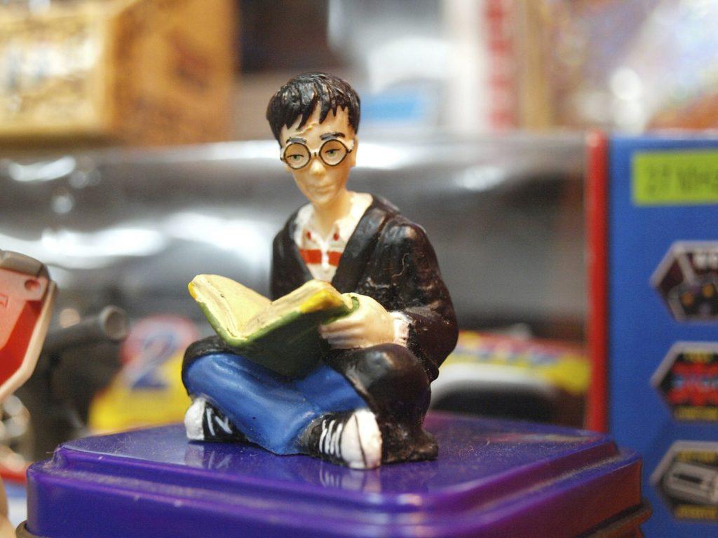 En liten leksaksfigur föreställer Harry Potter som sitter ner med en bok i famnen.