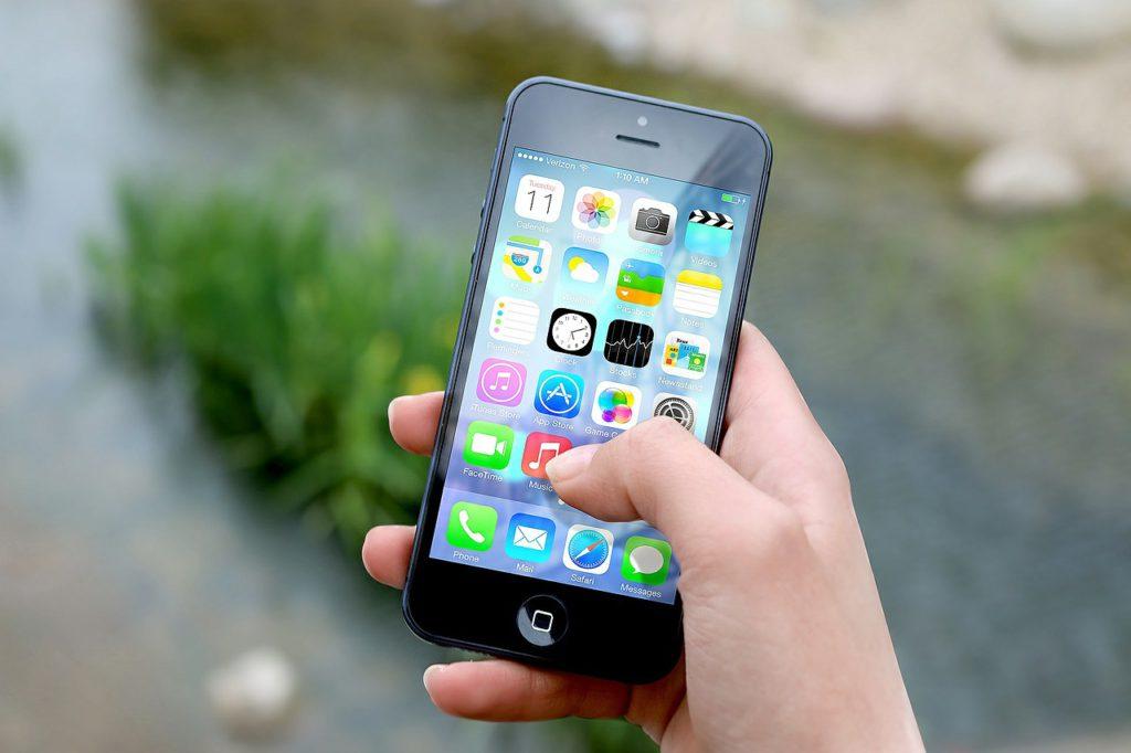 En person håller en smartphone i handen. På skärmen syns flera appar